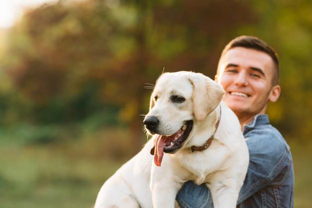 cara-segurando-seu-amigo-cachorro-labrador-e-sorrindo-ao-por-do-sol_8353-6467